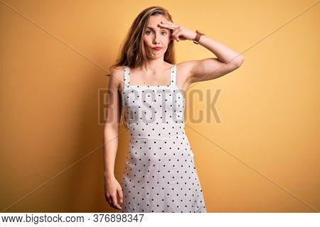 Young beautiful blonde woman on vacation wearing summer dress over yellow background worried and stressed about a problem with hand on forehead, nervous and anxious for crisis