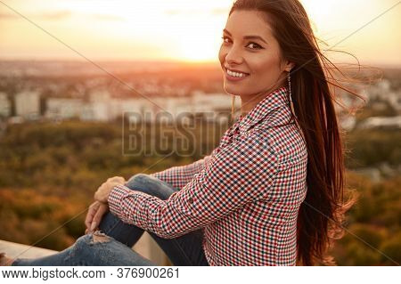 Side View Of Cheerful Young Female In Checkered Shirt Smiling And Looking At Camera On Blurred Backg