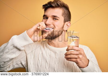 Young handsome caucasian man brushing his teeth using tooth brush, oral paste and glass of water, cleaning teeth and tongue as healthy health care morning routine