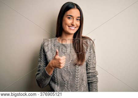Young beautiful brunette woman wearing casual sweater over isolated white background doing happy thumbs up gesture with hand. Approving expression looking at the camera showing success.