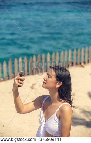 Young Beautiful Woman Spraying Thermal Water Or Facial Mist On Her Face At The Beach. Summer Skin Ca