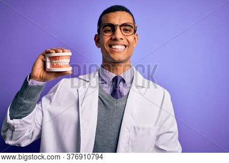 Young handsome african american dentist man holding denture teeth over purple background with a happy face standing and smiling with a confident smile showing teeth