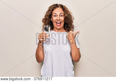 Middle age beautiful woman drinking glass of water to refreshment over white background pointing thumb up to the side smiling happy with open mouth