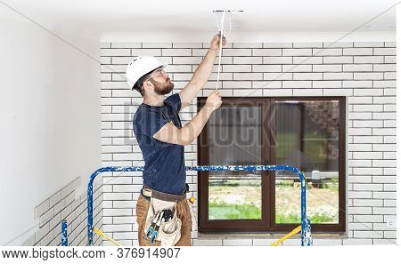 Electrician Builder At Work, Installation Of Lamps At Height. Professional In Overalls With An Elect