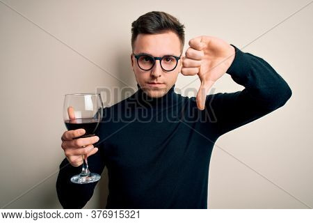 Young handsome caucasian man drinking an alcoholic glass of red wine over isolated background with angry face, negative sign showing dislike with thumbs down, rejection concept