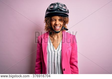 African american motorcyclist woman with curly hair wearing moto helmet over pink background winking looking at the camera with sexy expression, cheerful and happy face.
