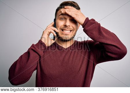 Young man with blue eyes speaking on the phone having a conversation on smartphone stressed with hand on head, shocked with shame and surprise face, angry and frustrated. Fear and upset for mistake.