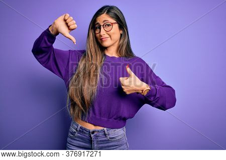 Young beautiful smart woman wearing glasses over purple isolated background. Doing thumbs up and down, disagreement and agreement expression. Crazy conflict
