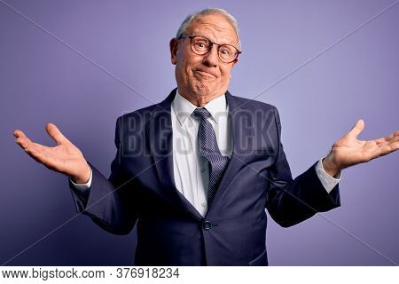 Grey haired senior business man wearing glasses and elegant suit and tie over purple background smiling showing both hands open palms, presenting and advertising comparison and balance