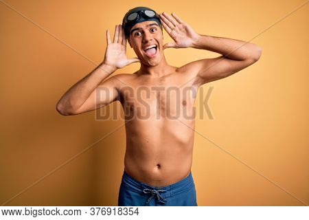 Young handsome man shirtless wearing swimsuit and swim cap over isolated yellow background Smiling cheerful playing peek a boo with hands showing face. Surprised and exited