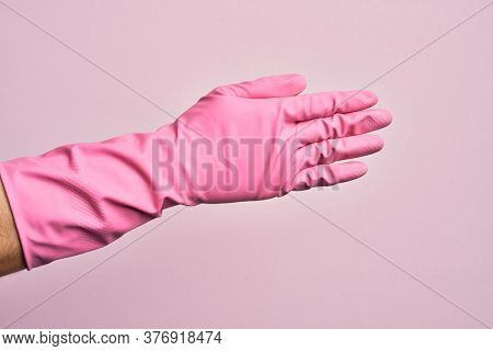 Hand of caucasian young man with cleaning glove over isolated pink background stretching and reaching with open hand for handshake, showing back of the hand
