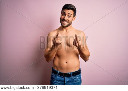 Young handsome strong man with beard shirtless standing over isolated pink background doing money gesture with hands, asking for salary payment, millionaire business