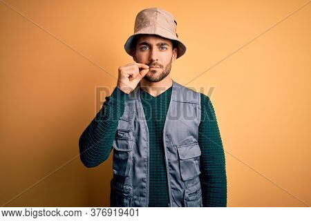 Handsome tourist man with beard on vacation wearing explorer hat over yellow background mouth and lips shut as zip with fingers. Secret and silent, taboo talking