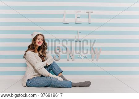 Female Photo In Studio With Blue And White Background. Adorable Christmas Girl In Mom Jeans And Knit