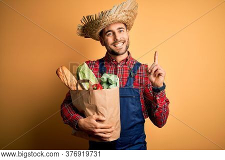 Young rural farmer man holding fresh groceries from marketplace over yellow background surprised with an idea or question pointing finger with happy face, number one