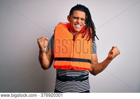 Young african american afro man with dreadlocks wearing orange lifejacket very happy and excited doing winner gesture with arms raised, smiling and screaming for success. Celebration concept.