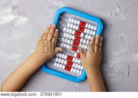 Girl Holding Plastic Abacus, Copy Space. Flat Lay, Children Home Education