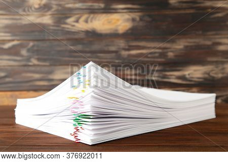 Colorful Paper Clip With Pile Of Overload White Paperwork On Brown. Top View