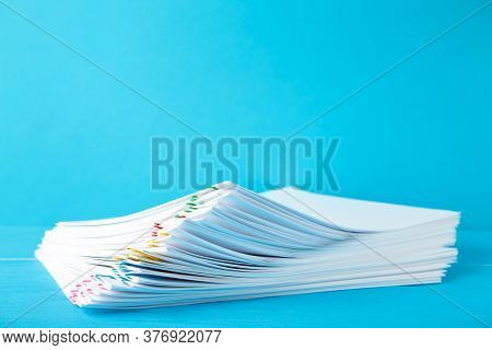 Colorful Paper Clip With Pile Of Overload White Paperwork On Blue. Top View