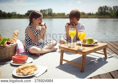 Children on wooden  pier eat watermelon.
