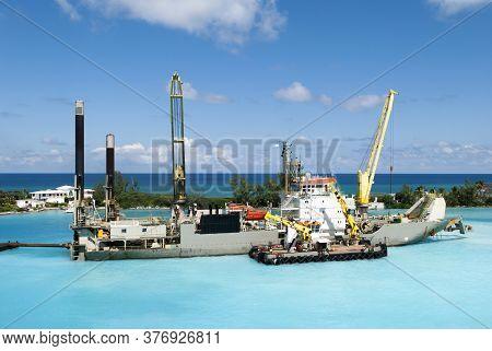 Industrial Ship With Tall Cranes Working Inside Nassau Harbour Along Paradise Island Coastline (baha