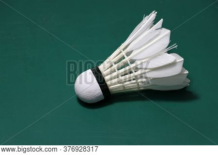 Used Shuttlecock Put Horizontal On Green Floor Of Badminton Court. Badminton Sport Concept.