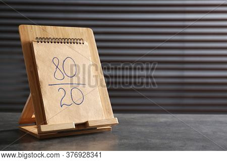 Notebook With 80/20 Rule Representation On Grey Stone Table, Space For Text. Pareto Principle Concep