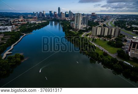Aerial Views Of Austin Texas Above Colorado River With Downtown Skyline And Boats In The Waters Of L