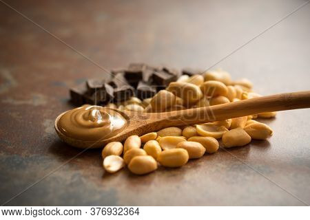 Still Life Photo Showing Delicious Chocolate And Peanuts With A Spoon Full Of Peanut Butter On A Bro