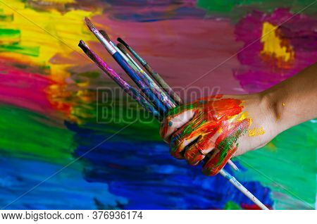 Close Up Of An Artist Or Painter Hands Holding Dirty Paint Brushes On Colorful Picture