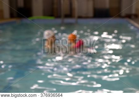 Blurred Images Of Teacher And Kid Teaching To Swim In Pool