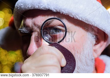 Santa Looks Through Lens. Bearded Man In Santa Hat Holds Magnifying Glass. Santa Claus Looking Throu