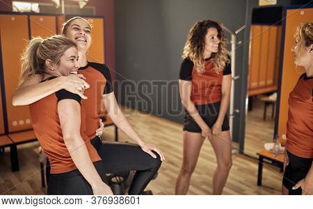 Smiling team girls  in changing room.Sporty woman preparing for game in locker room.