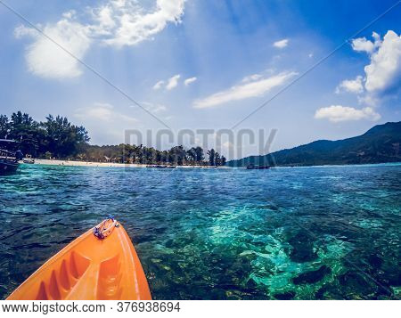 kayaking in crystal clear tropical waters - kayak heading to isolated beach in Ko Tarutao national park