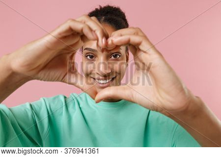 Smiling Young African American Girl In Green Sweatshirt Posing Isolated On Pastel Pink Wall Backgrou