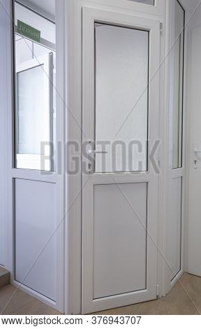 White Pvc Doors And A Green Sign With The Inscription Exit.