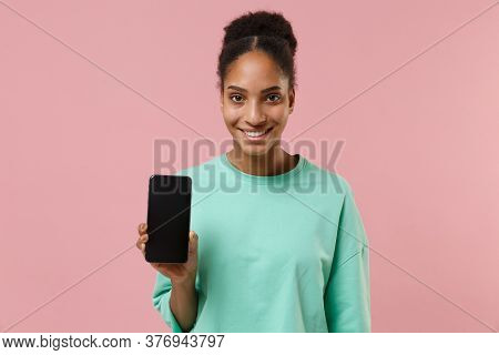 Smiling Young African American Woman Girl In Green Sweatshirt Posing Isolated On Pastel Pink Wall Ba