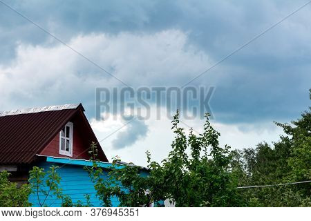 The Roof Of A Village House And Tree Branches During Bad Weather. Dark Clouds Before Rain In The Cou