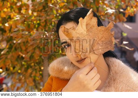 Autumn Portrait Of Cute Arabian Woman Covering One Eye With Big Fall Leaf. Autumn Garden And Beautif