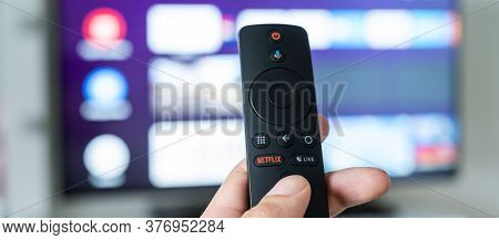 A Man Holds A Remote Control In His Hand With The Netflix Logo On The Background Of A Blurred Televi