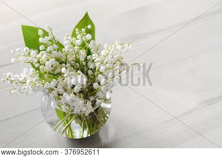 Fragrant Lilly Of The Valley Bunch In The Glass Vase On The White Table. Copy Space