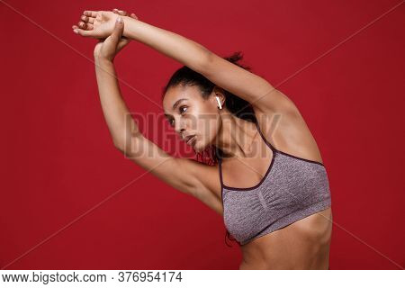 Beautiful African American Sports Fitness Woman In Sportswear Working Out Isolated On Red Background