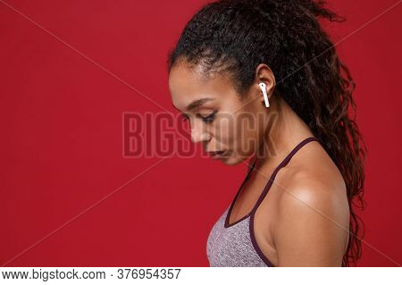 Side View Of Young African American Sports Fitness Woman In Sportswear Working Out Isolated On Red W