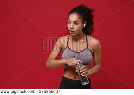 Strong Young African American Fitness Woman In Sportswear Posing Isolated On Red Background. Sport E