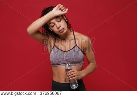 Tired African American Fitness Woman In Sportswear Isolated On Red Background. Sport Exercises Healt