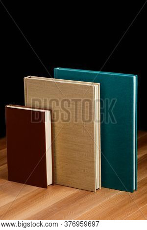 Hardcover Books On The Wooden Table. Different Size And Color Of Cover
