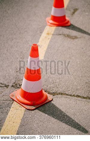 Orange Traffic Cones Stand On The Asphalt In A Line, Close-up.