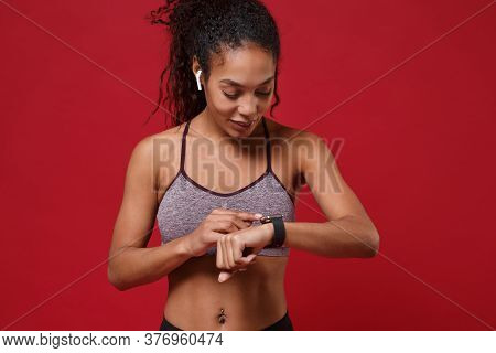 Smiling Young African American Sports Fitness Woman In Sportswear Working Out Isolated On Red Backgr