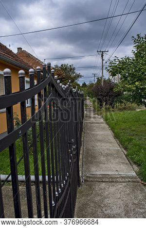 Street Sidewalk And A Beautiful Black Metal Fence.