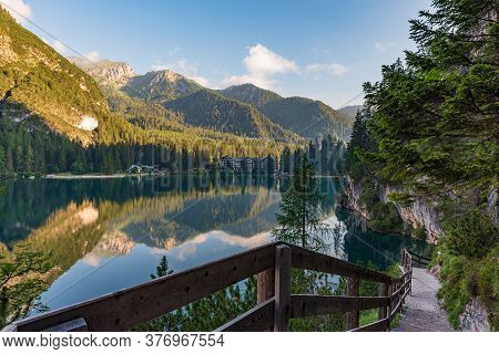 A Path With A Wooden Fence Climbs Steeply Beside The Braies Lake
